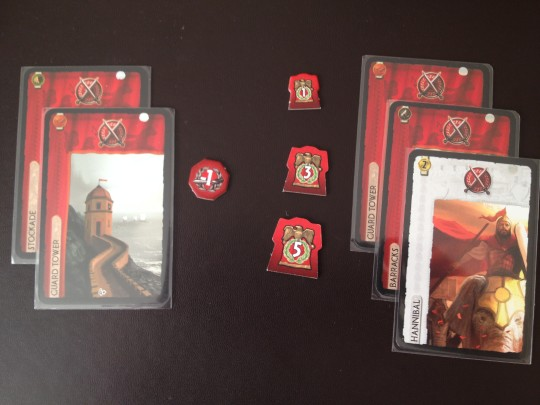 The player on the left has 2 Military Strength from their Stockade and Guard Tower. The player on the right has 3 from their Guard Tower, Barracks and their Leader, Hannibal. The left player will lose 1 point and the right player will gain 1,3 or 5 points depending on the current Age.