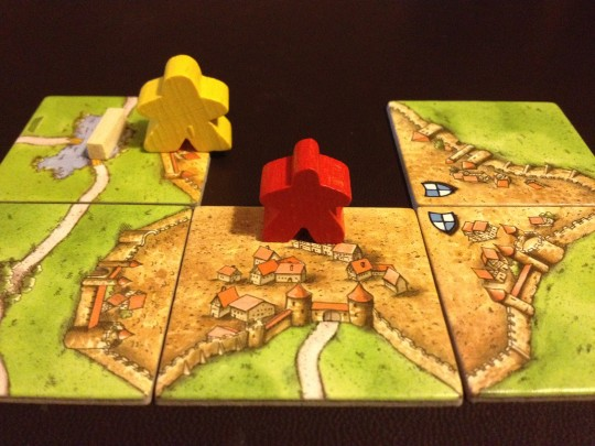 The Yellow player has played his large Meeple as a Knight in the hope of stealing the City, and points away from the Red player.
